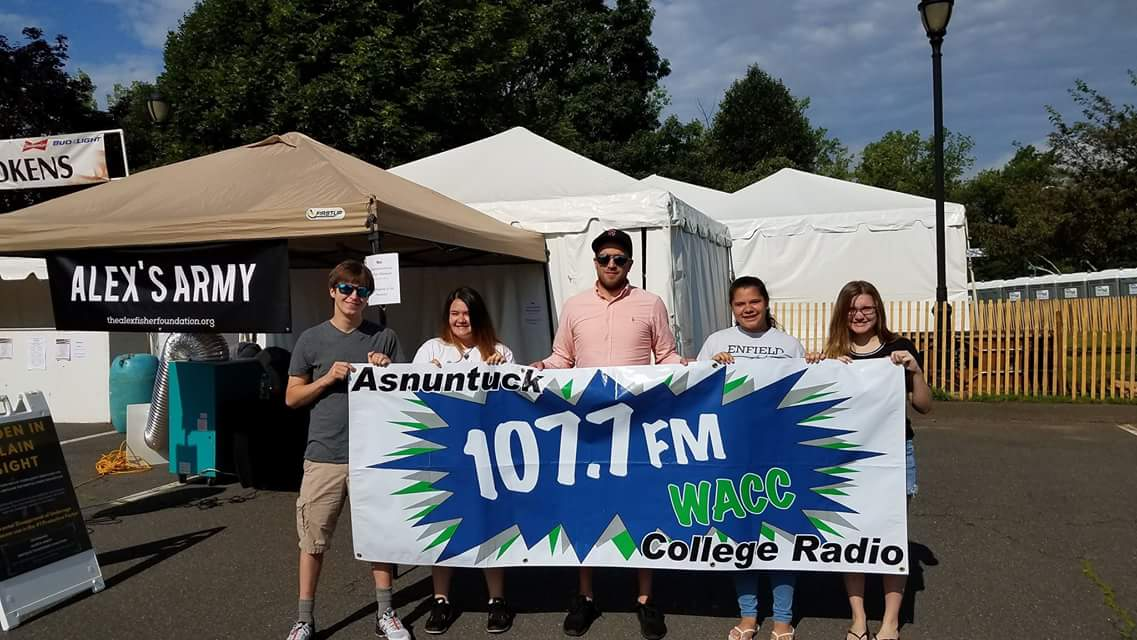 Teens Holding Asnuntuck 107.7 FM College Radio Banner